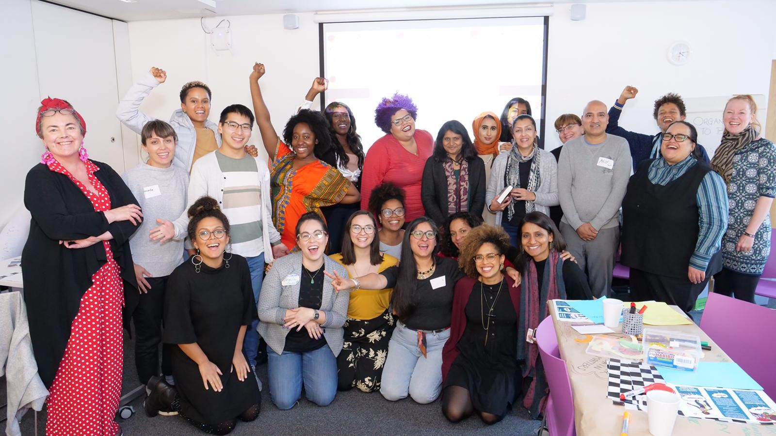 A group photo of 24 workshop attendees, mostly women of colour, all skin tones and hair colours with colourful outfits, big smiles and positive energy. An Asian woman has an orange hijab, while a black woman is wearing a dashiki. few of them are holding up their right fists or a peace sign.
